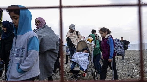 Un grupo de refugiados llega un campo de registro en la frontera entre Grecia y Macedonia.EFE